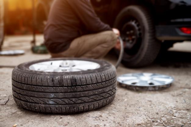Neumático nuevo tirado en el pavimento cerca del mecánico listo para reemplazar el de un automóvil.