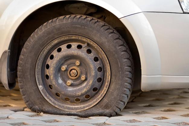 Neumático pinchado del coche en el pavimento. vista lateral al aire libre del vehículo de cerca.