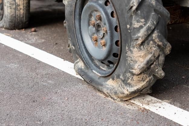 Neumático pinchado del tractor en la carretera de asfalto, rueda grande del automóvil, espera reparación, mantenimiento en el transporte agrícola