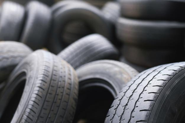 Neumáticos usados viejos apilados con pilas altas. cerrar dañado negro desgastado neumático de la banda de rodadura del coche