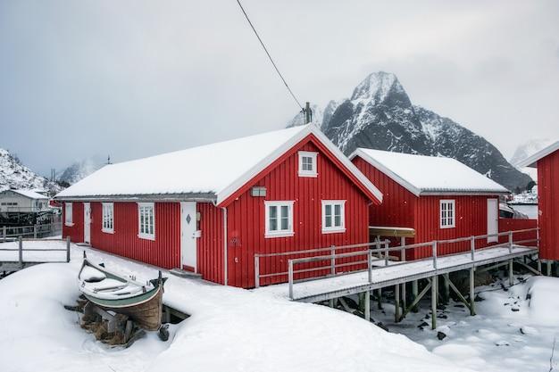Nevado en casa roja en el puerto en el valle