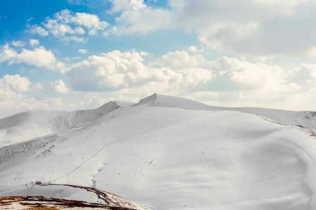 Nevados hermosos picos de las montañas con cielo azul