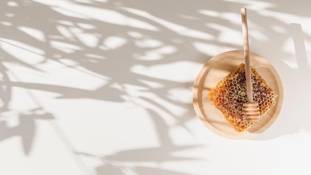 Nido de abeja con cucharón de miel en placa de madera sobre la sombra de hojas en la pared
