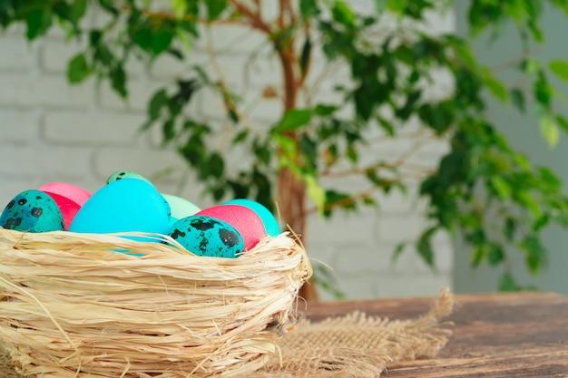 Nido decorativo de pascua con huevos de colores de cerca