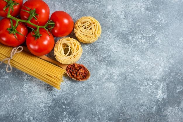 Nido de espaguetis crudos con verduras sobre un fondo de mármol