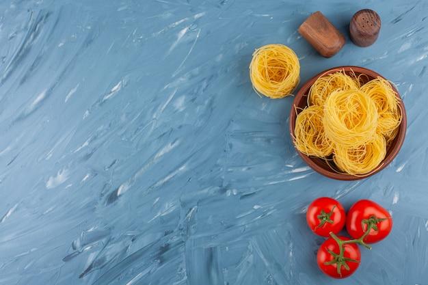 Nido de fettuccine de pasta italiana con tomates rojos frescos y especias.