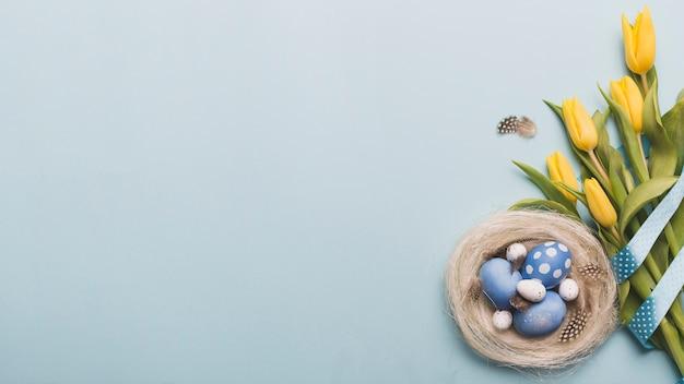 Nido con huevos de colores cerca de tulipanes