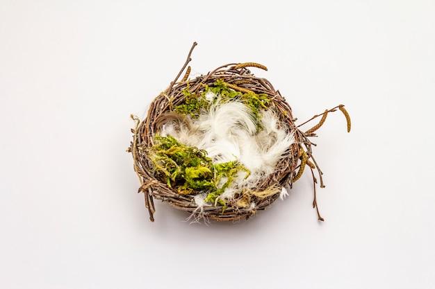 Nido de pájaro de pascua aislado sobre fondo blanco. cero desperdicio, concepto de bricolaje. plumas suaves, musgo