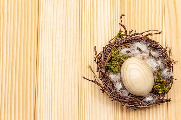 Nido de pájaro de pascua. cero desperdicio, concepto de bricolaje. huevo de madera, plumas, musgo. fondo de tableros
