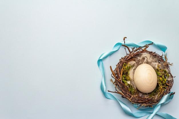 Nido de pájaro de pascua. cero desperdicio, concepto de bricolaje. plumas suaves, huevo, musgo. fondo azul claro