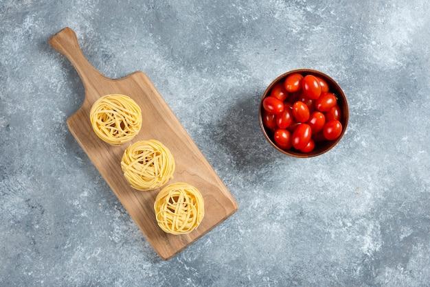 Nido de pasta sobre tabla de madera con plato de tomates.
