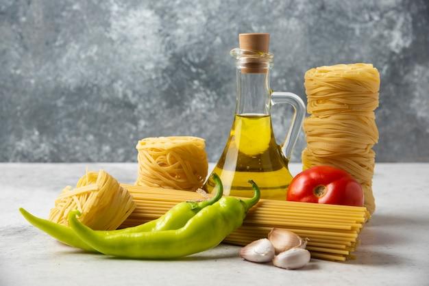 Nidos de pasta cruda, espaguetis, botella de aceite de oliva y verduras sobre superficie blanca.