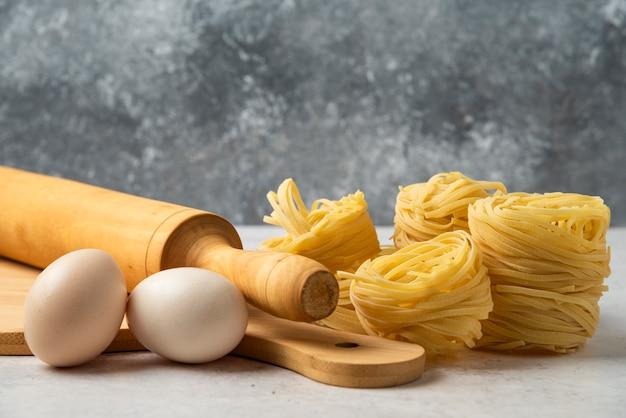 Nidos de pasta cruda, huevos, tablero de madera y rodillo sobre mesa blanca.