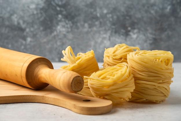 Nidos de pasta cruda, tablero de madera y rodillo sobre mesa blanca.