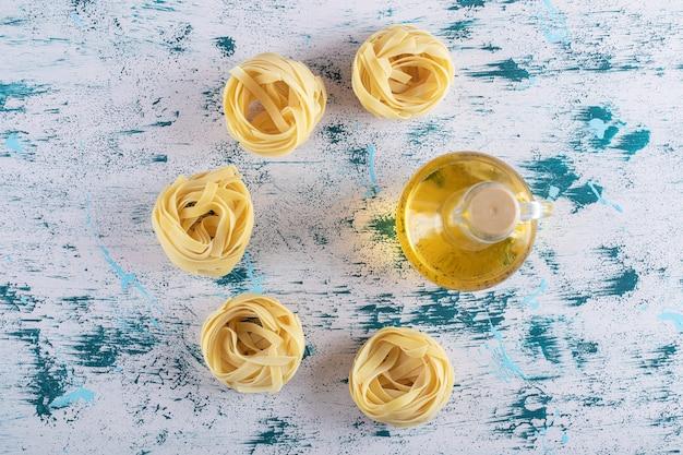 Nidos de tallarines y vaso de aceite de oliva sobre fondo de colores. foto de alta calidad