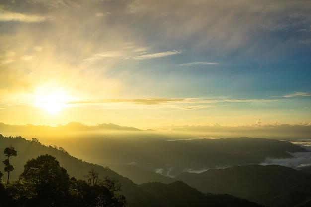 Niebla en montañas, fantasía y naturaleza colorida paisaje y rayo de sol a través de las nubes