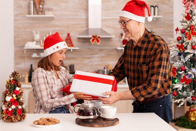 Nieta abuelo sorprendente con regalo de envoltura celebrando la fiesta de navidad