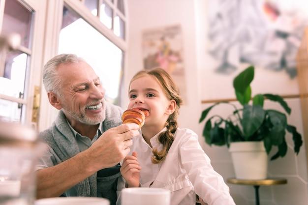 Nieta divertida. abuelo canoso barbudo que se siente alegre mirando a su nieta divertida