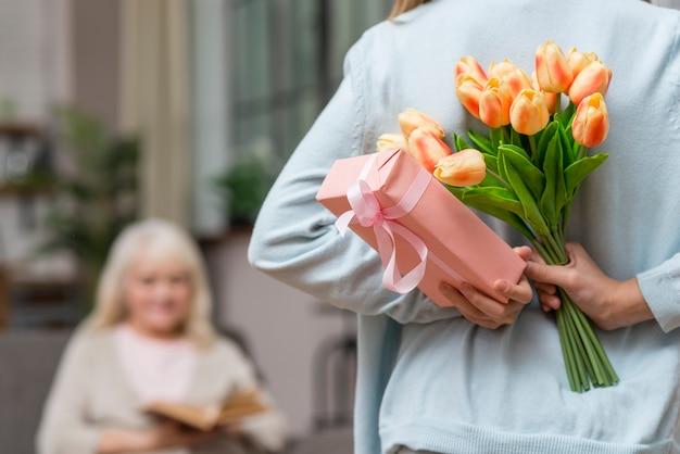 Nieta escondiendo un regalo y abuela leyendo