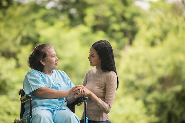 Nieta hablando con su abuela sentada en silla de ruedas, concepto alegre, familia feliz