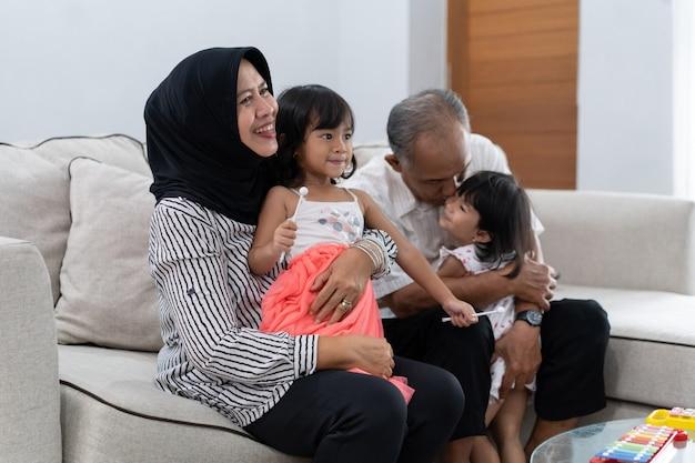 Nieta en el regazo de la abuela y abuelo abrazó a otra nieta