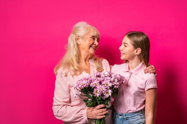 Nieto y abuela abrazando con un ramo de flores