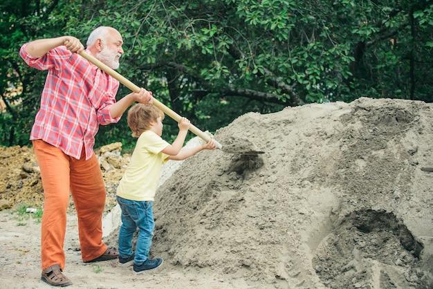Nieto ayudando a su abuelo con las obras de construcción. concepto de infancia. futuro nieto trabajador con abuelo. niño y obra. trabajador de nieto con pala. ayuda para el abuelo.