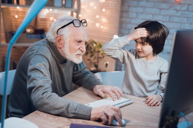 Nieto enseñando a un abuelo a usar la computadora