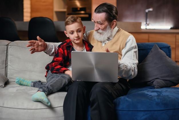 Nieto le está enseñando a su abuelo a usar una computadora portátil.
