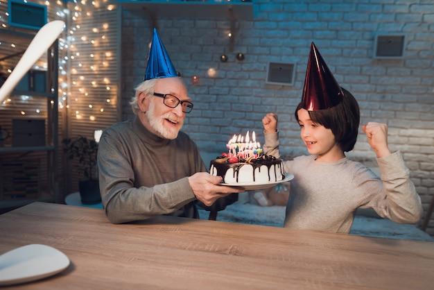 Nieto soplando velas en el pastel de cumpleaños
