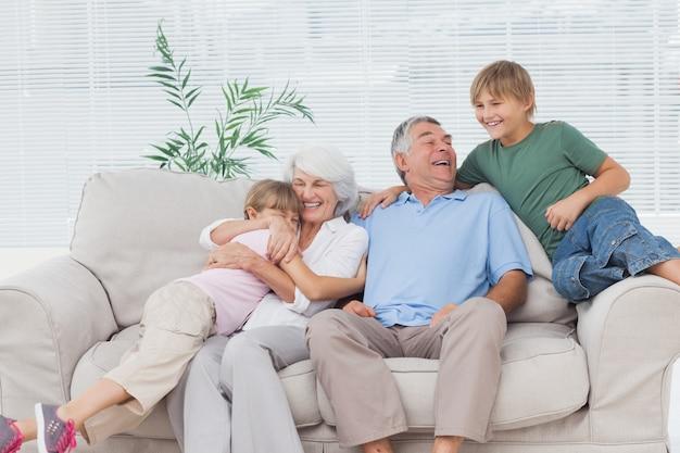 Nietos sonrientes que abrazan a sus abuelos