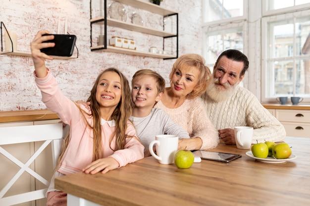Nietos tomando una selfie con sus abuelos.