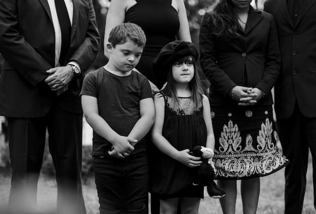Nietos tristes de pie junto a la tumba