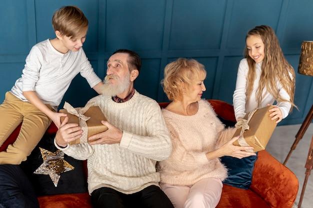 Nietos de vista frontal dando regalos a sus abuelos