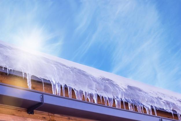 La nieve del techo se derrite en carámbanos bajo el sol primaveral.