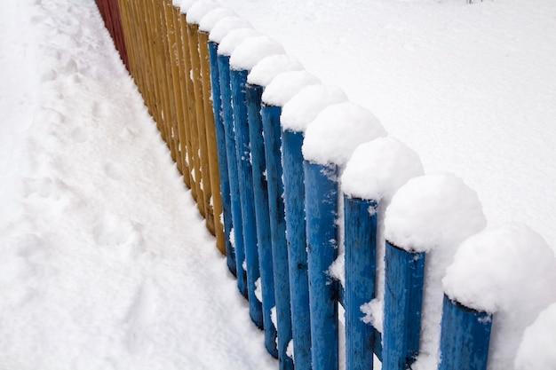 Nieve en una valla de madera. valla de madera rústica cubierta de nieve.