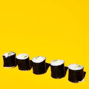 Nigiri rolls sobre un fondo amarillo