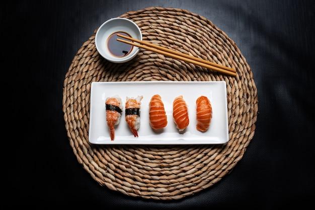 Nigiri sushi en un plato de cerámica blanca con palillos y un tazón con salsa de soja sobre un mantel de mimbre redondo sobre un fondo negro.