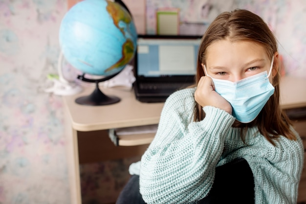 Niña de 10 años con una máscara sobre educación a distancia en casa. el niño está aburrido, está cansado