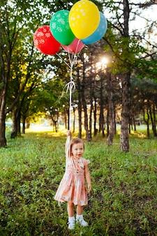 Niña 2-3 años sosteniendo globos al aire libre. fiesta de cumpleaños. infancia. felicidad.