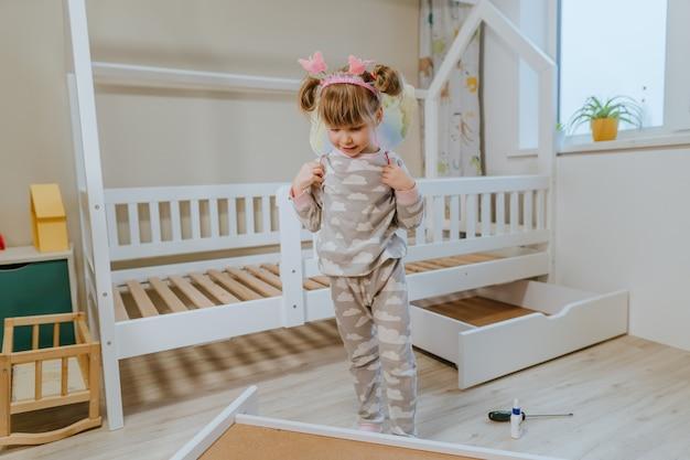 Niña de 4 años en pijama y disfraz de alas de mariposa jugando en el dormitorio de los niños junto a la cama nueva.