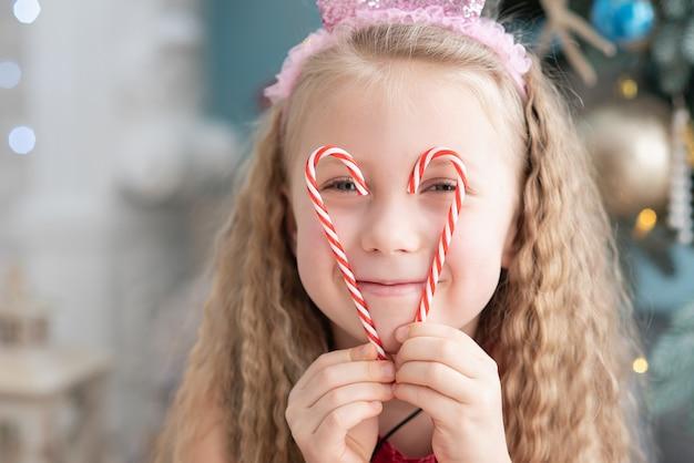 Niña de 5 años con dulce lollipop candy cane cerca del árbol de navidad.