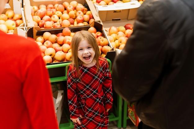 Una niña de unos 5 años hizo una rabieta en un supermercado frente a sus padres. el niño grita y llora, pidiendo dulces a mamá y papá