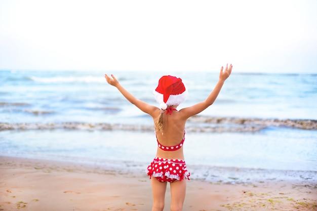 Niña de 5 años en traje de baño rojo y gorro de papá noel en la playa es feliz, grita, salta y agita las manos con felicidad. viajes invernales de navidad y año nuevo a países cálidos. turismo para vacaciones en los trópicos