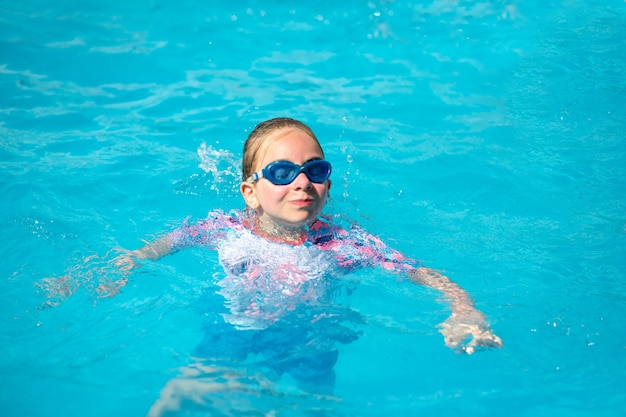 Niña de 8 años, con un traje de baño brillante y gafas azules, nada en una piscina bajo el sol con agua azul, feliz y feliz