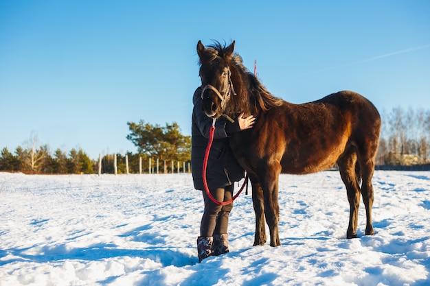 Niña abraza el caballo negro árabe. campo de invierno cubierto de nieve en un día soleado