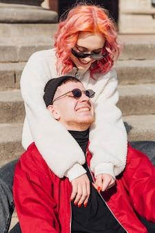 Niña abrazando y mirando a su novio mientras está sentado en las escaleras