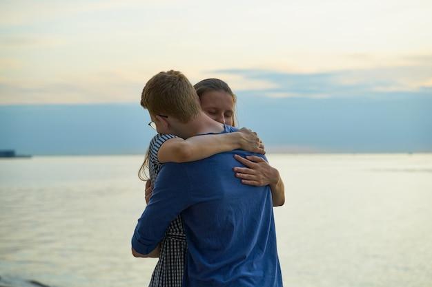 Niña abrazando a niño en la playa, amor adolescente en la puesta del sol