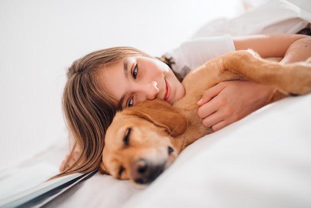 Niña abrazando perro en la cama
