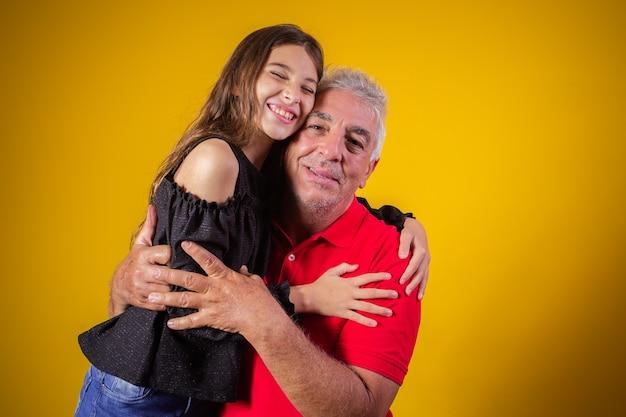 Niña abrazando a su abuelo. padre e hija sobre fondo amarillo. dia del padre. dia del abuelo